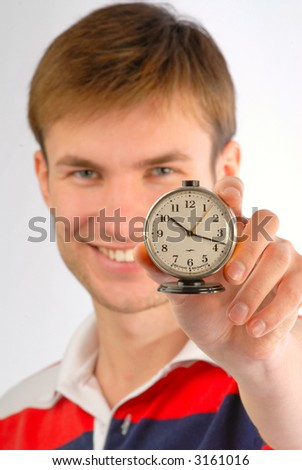 young nice, smiling guy with an alarm clock in hands, close up - stock photo