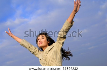 young nice woman with  lifted hands on  background of  blue sky