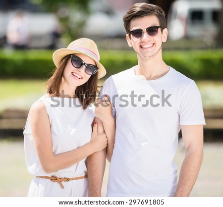 Young nifty couple walking along the street on summer day. - stock photo