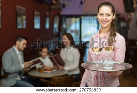 young nippy with beverages and bar crew at background - stock photo