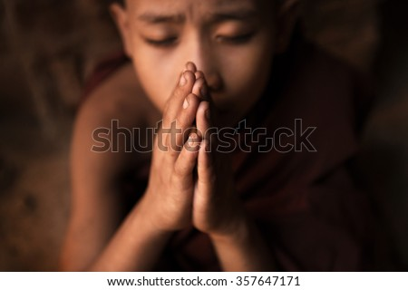 Young novice monk praying inside Buddhist temple, low light with noise setting, Bagan, Myanmar. - stock photo