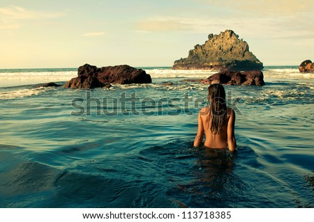 Young nude woman in the sea - stock photo