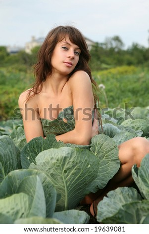 Young nude woman sit in cabbage field.