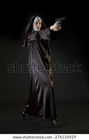Young nun shooting from gun. Low key photo on black background. Dynamic full growth photo. - stock photo