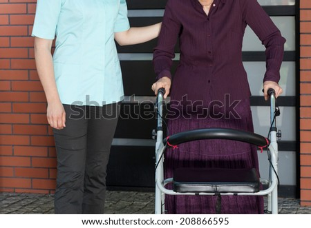 Young nurse and elderly woman in a walker outside - stock photo