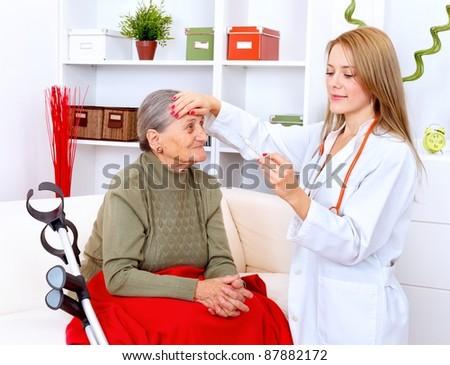 Young nurse checking body temperature for a senior woman - stock photo