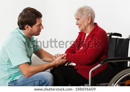 Young nurse full of compassion assisting lady on wheelchair  - stock photo