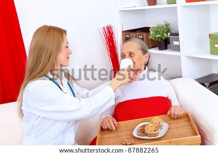 Young nurse helping elderly woman to drink - stock photo