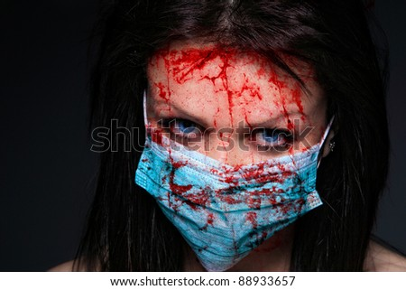 Young nurse in mask covered of blood - stock photo