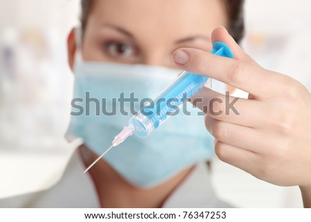 Young nurse in mask with syringe - stock photo