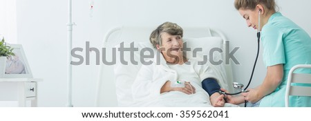 Young nurse measuring blood pressure to older woman - stock photo