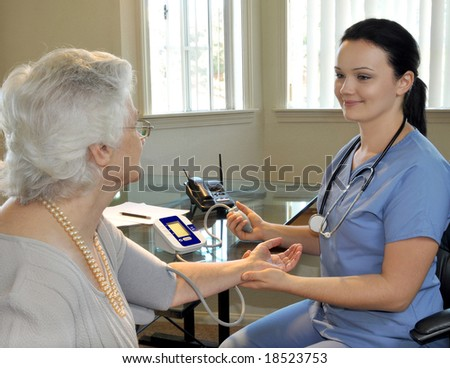 young nurse measuring the patient's blood pressure - stock photo