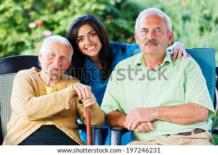 Young nurse or doctor with an elderly woman and a relative of her in the garden of the nursing home. - stock photo
