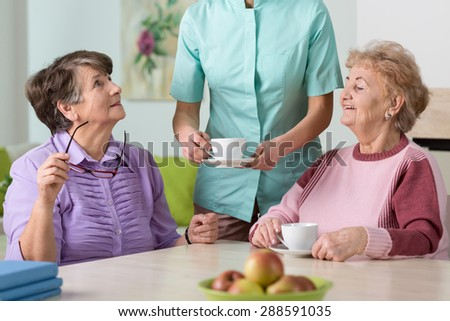 Young nurse serving hot tea to her two senior wards - stock photo