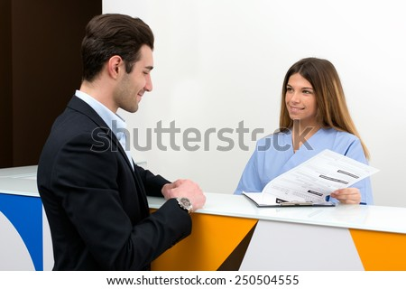 young nurse speaking with client and show him medical information : they discussing together on medical exam at hospital