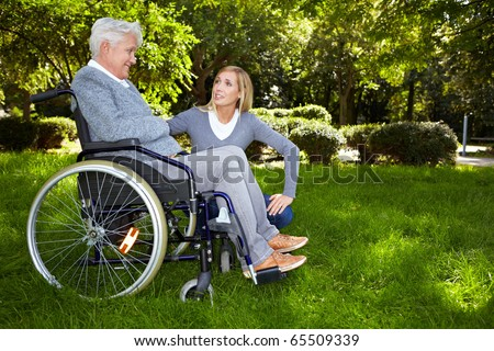 Young nurse talking to woman in wheelchair in park - stock photo