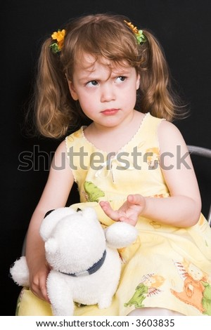 young offended girl in yellow dress with toy