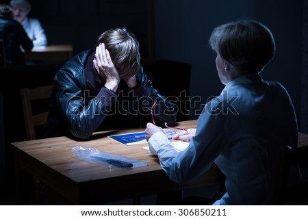 Young offender covering ears during police interrogation - stock photo