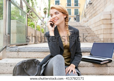 Young office business woman using a smart phone on a phone call conversation, with laptop technology sitting in a city stone stairs, outdoors. Professional woman speaking on cell, sunny exterior.