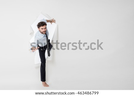 young office man with tie and barefoot breaking the paper background, passing from side to side