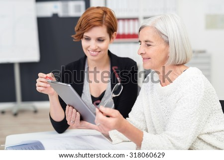 Young Office Woman Teaching her Senior Female Colleague on how to Use Tablet Computer Inside the Workplace. - stock photo