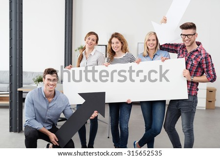 Young Office Workers Holding White Reactangular Poster with Copy Space and and a Black Arrow Cutout, Smiling at the Camera. - stock photo