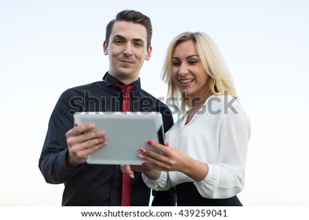 Young office workers watching tablets on the background the city  - stock photo