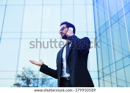 Young official man expert calling via cell telephone while standing outdoors near modern glass building, young male employer talking on mobile phone about unsuccessful project after presentation  - stock photo