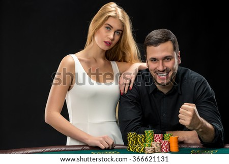 Young ?ouple playing poker and have good time in casino - stock photo