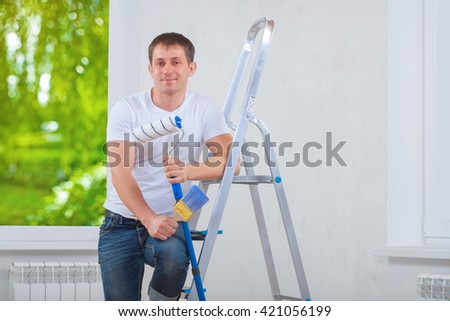 young painter holding paintroller and paintbrush standing near stepladder. - stock photo