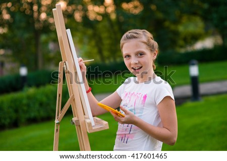 Young painter with her easel is going to create her new masterpiece. Lovely hobby of a little talent. Gentle smile of little girl. Perfect retouching of the photo. - stock photo
