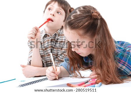 Young painters. Small pretty girl lying on the floor drawing with colorful felt-tip pens in a sketchbook and her older brother wondering what to draw holding a pencil in his mouth - stock photo