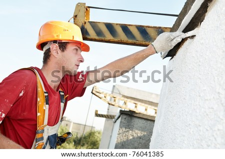 Young painting facade builder worker with brush in work wear - stock photo