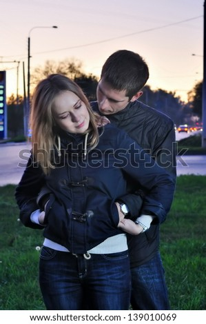 young pair embraces in the evening near the road - stock photo
