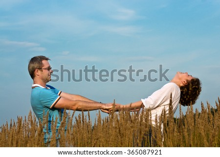 young pair holds hands on a meadow - stock photo