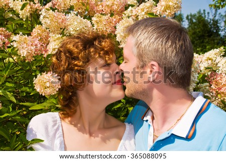 young pair kisses in a flowers - stock photo