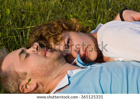 young pair lies on a grass - stock photo