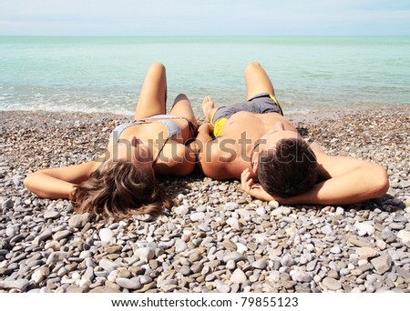 Young pair lies on to the beach - stock photo