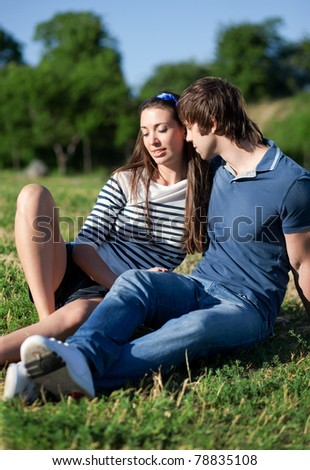 Young pair, man and woman relax in park