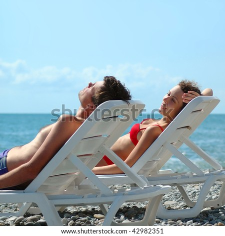 Young pair reposes in chaise lounge on beach - stock photo