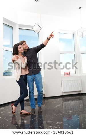 young pair, searching the real estate for a purchase - stock photo