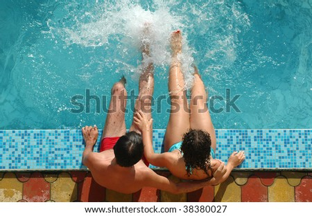 Young pair sits beside water pool - stock photo