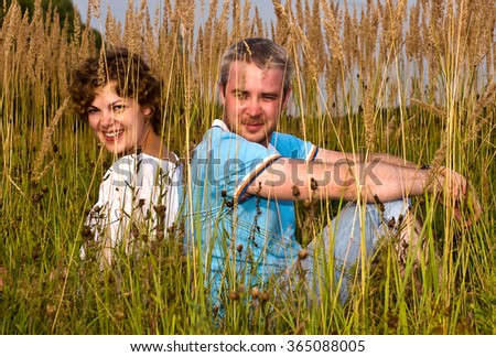 young pair sits on a grass, a back to a back - stock photo