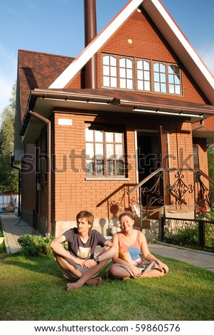 young pair sitting near house