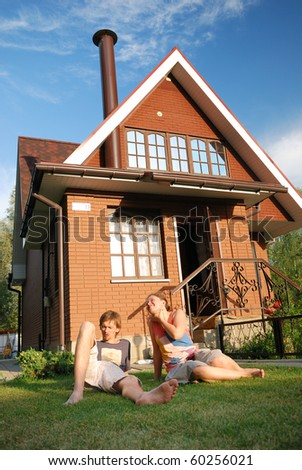 young pair sitting near house - stock photo