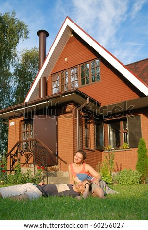 young pair sitting near new their house - stock photo