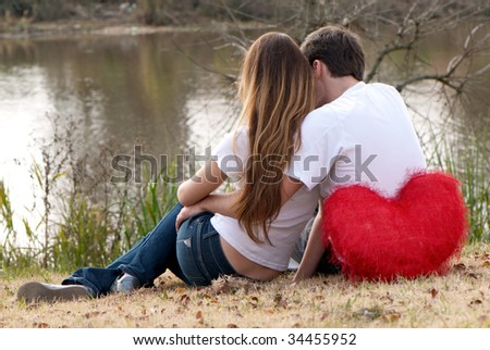 Young pair sitting on bank of lake - stock photo