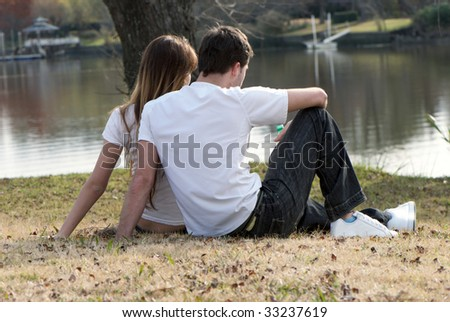 Young pair sitting on the bank of lake - stock photo