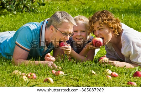 young pair with child bites apple, lie on a grass - stock photo