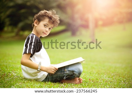Young pan asian boy enjoying his reading book in outdoor park - stock photo